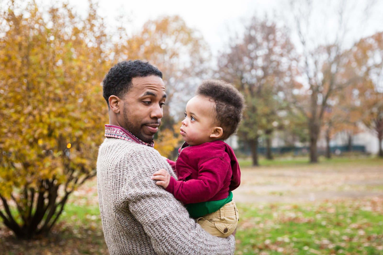 Flushing Meadows Corona Park family portrait of father and son looking at each other