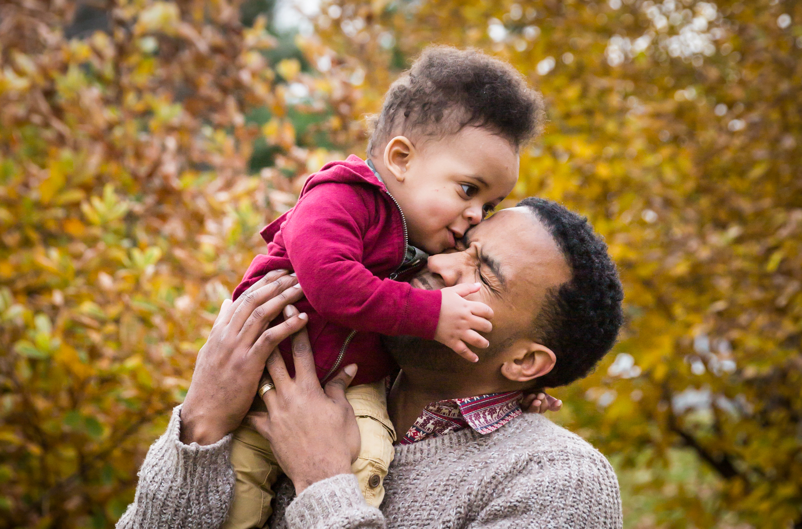Flushing Meadows Corona Park family portrait of son kissing father's face