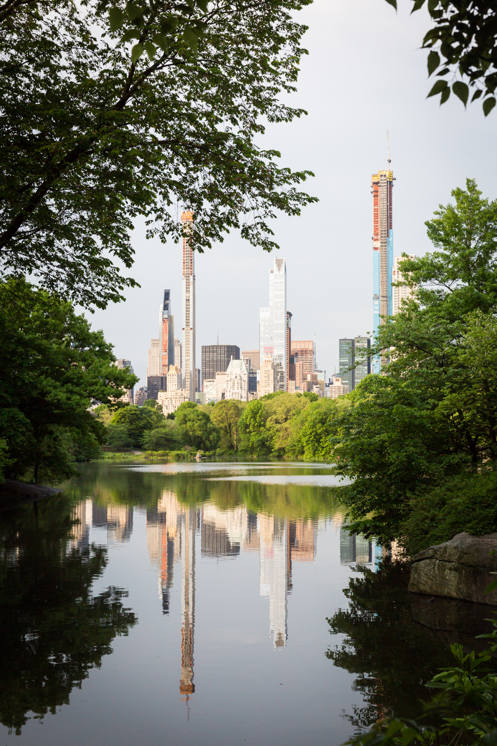 View of NYC skyline across Central Park lake