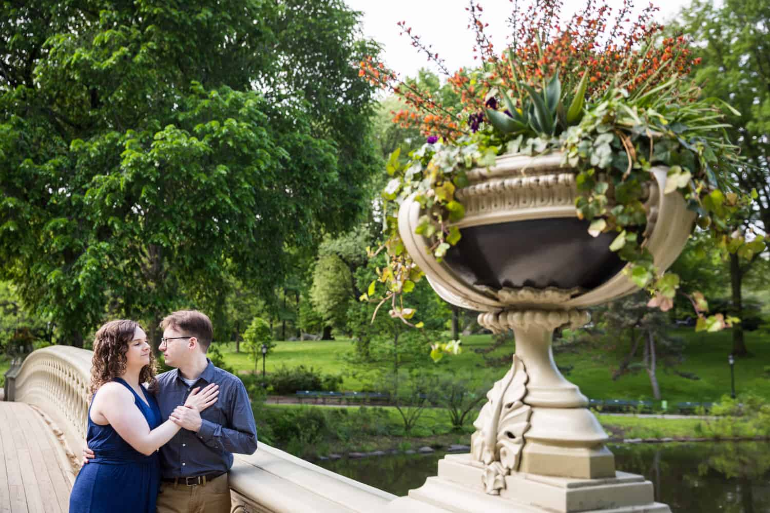 Couple hugging on Bow Bridge for Shakespeare Garden engagement photos