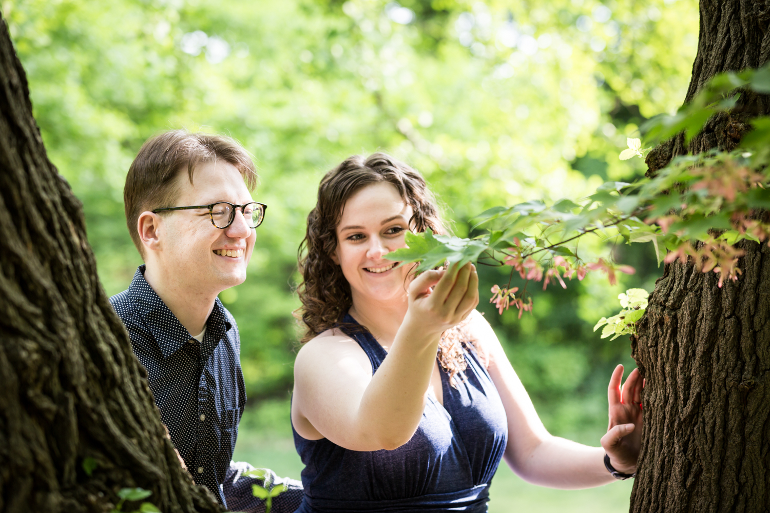 Woman showing leaves to man in Central Park Shakespeare Garden engagement photos