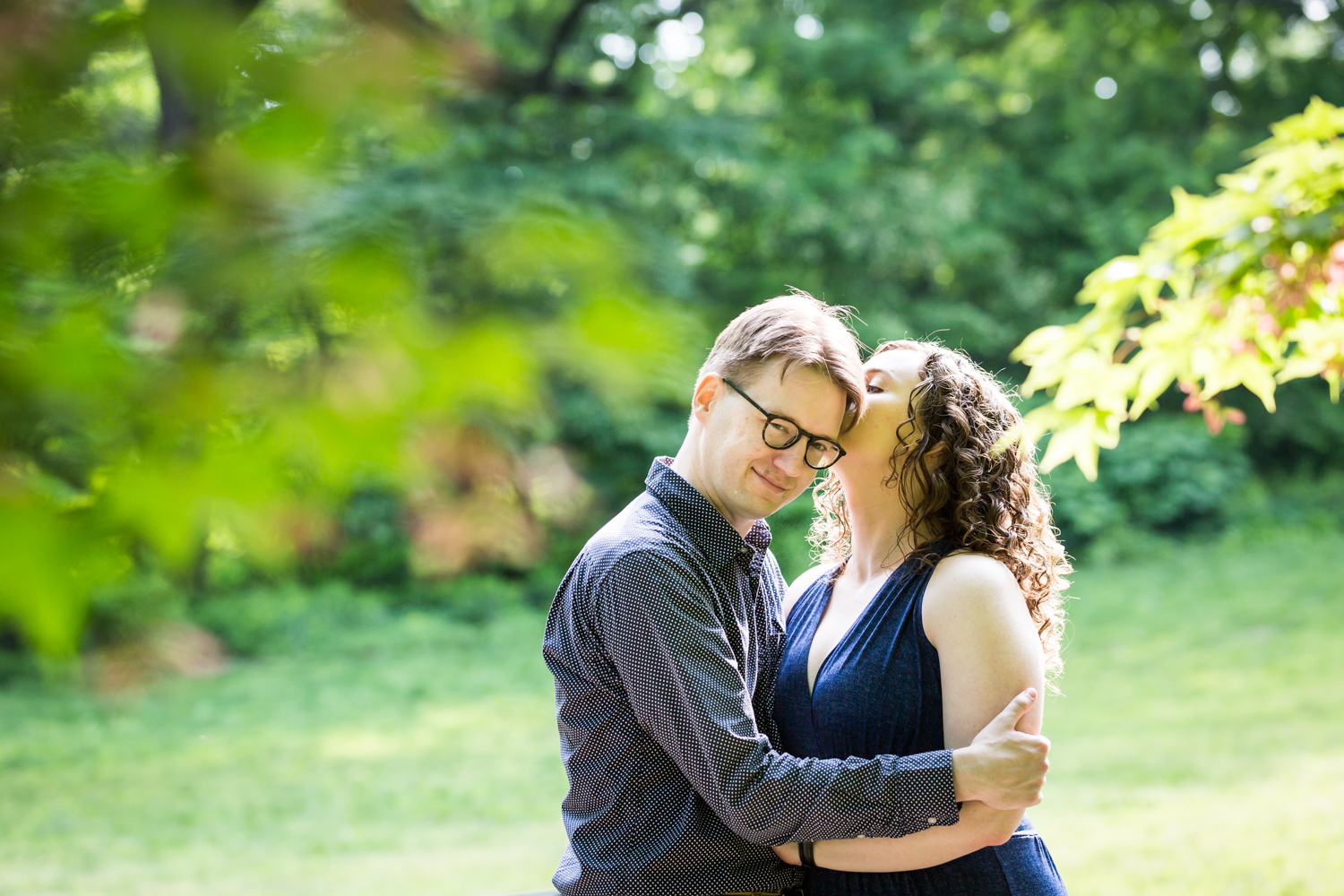 Woman kissing man through leaves in Central Park