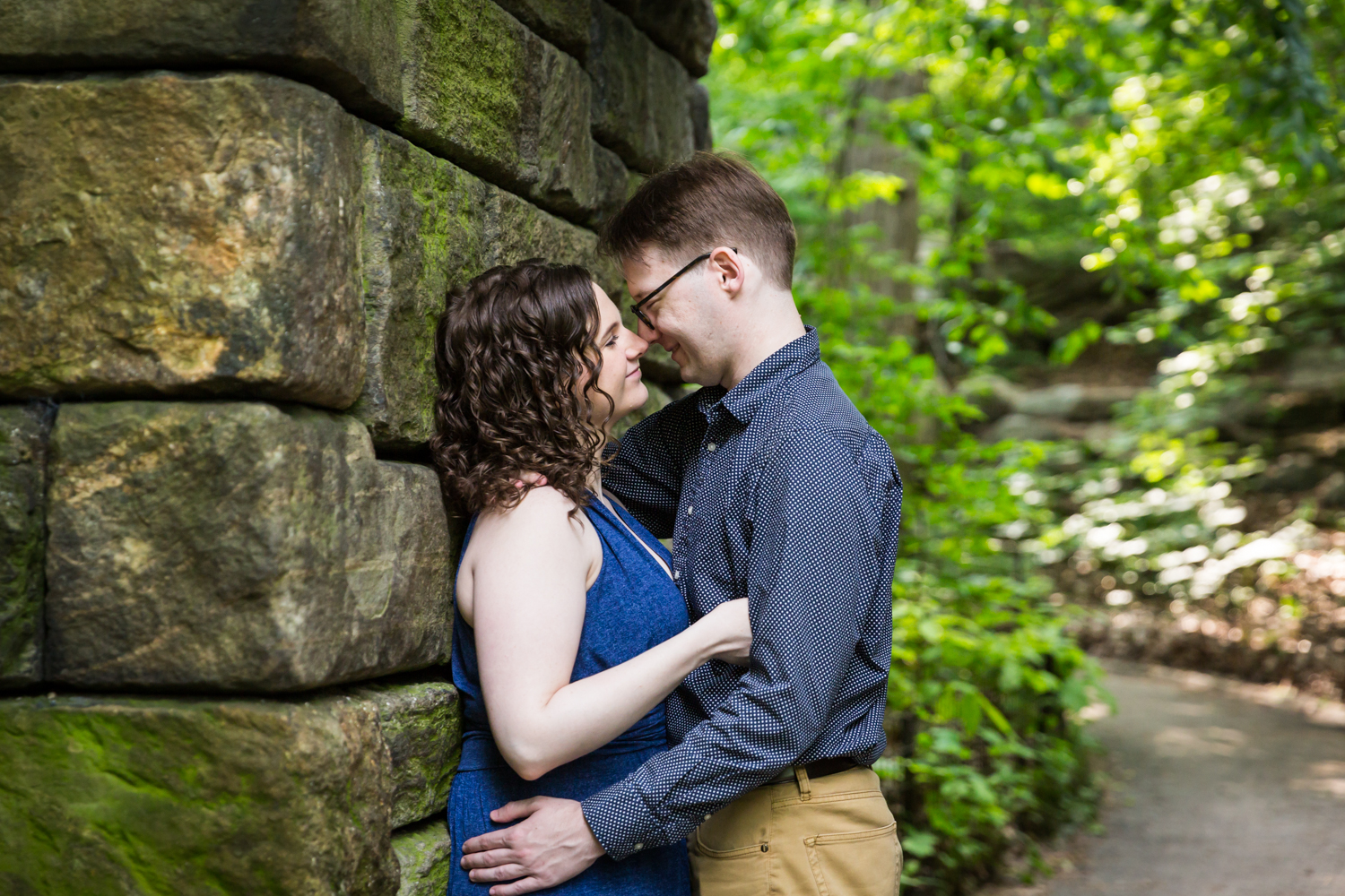 Couple leaning up against the wall of the Ramble Stone Arch