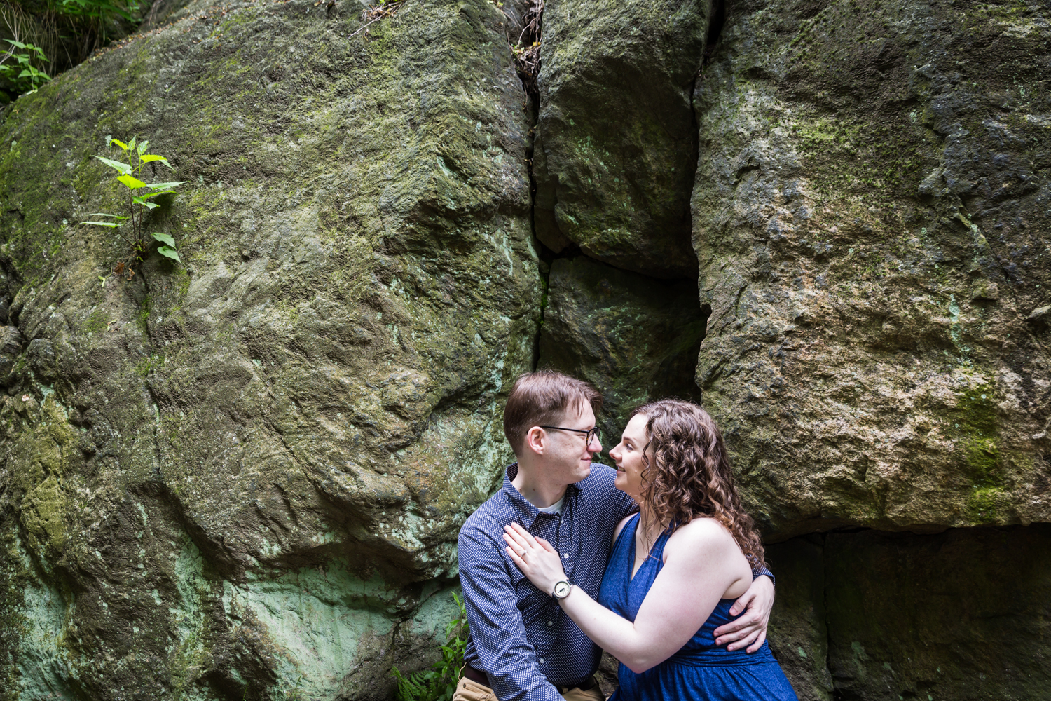 Couple sitting by boulders next to Ramble Stone Arch