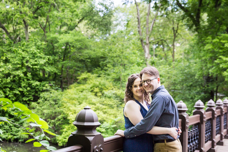 Couple hugging on Oak Bridge in Shakespeare Garden engagement photos
