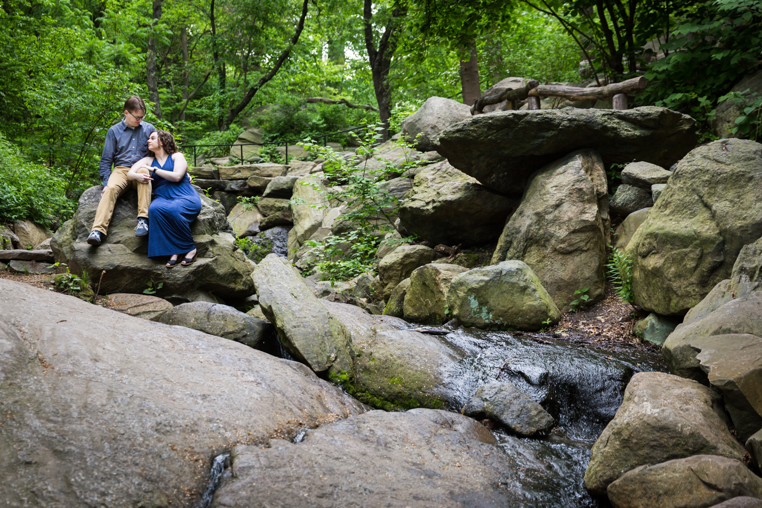 Couple sitting on boulders beside waterfall in Central Park