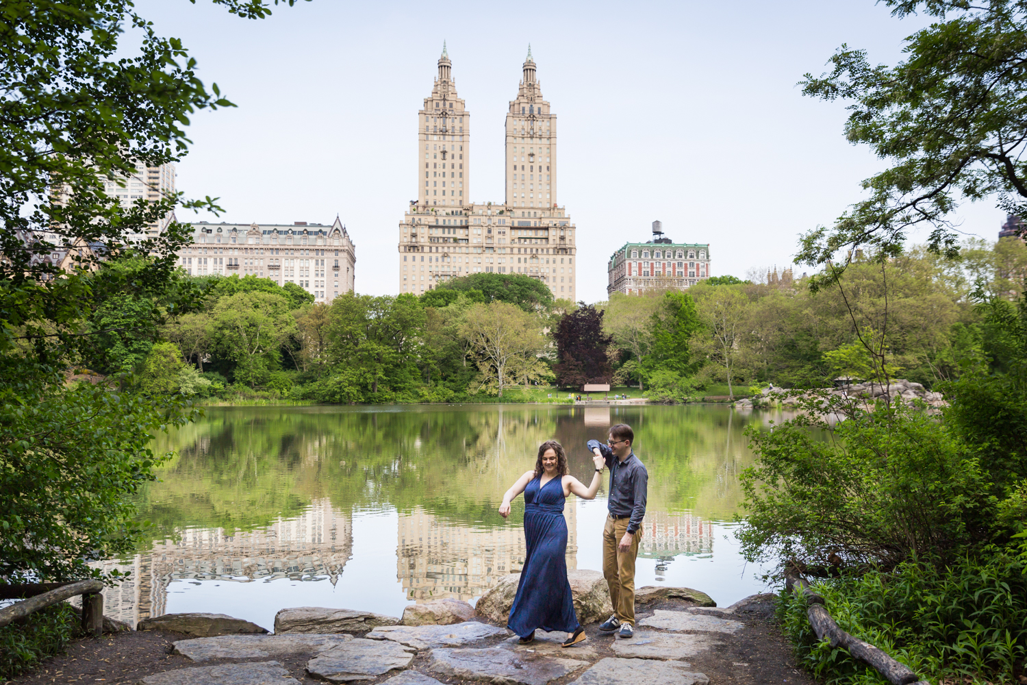 Couple dancing at Central Park lake viewing area in Shakespeare Garden engagement photos