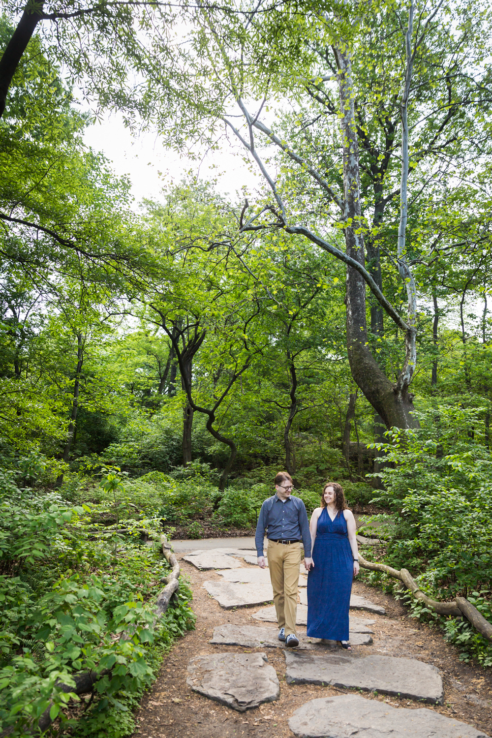 Couple walking down stone path in Central Park