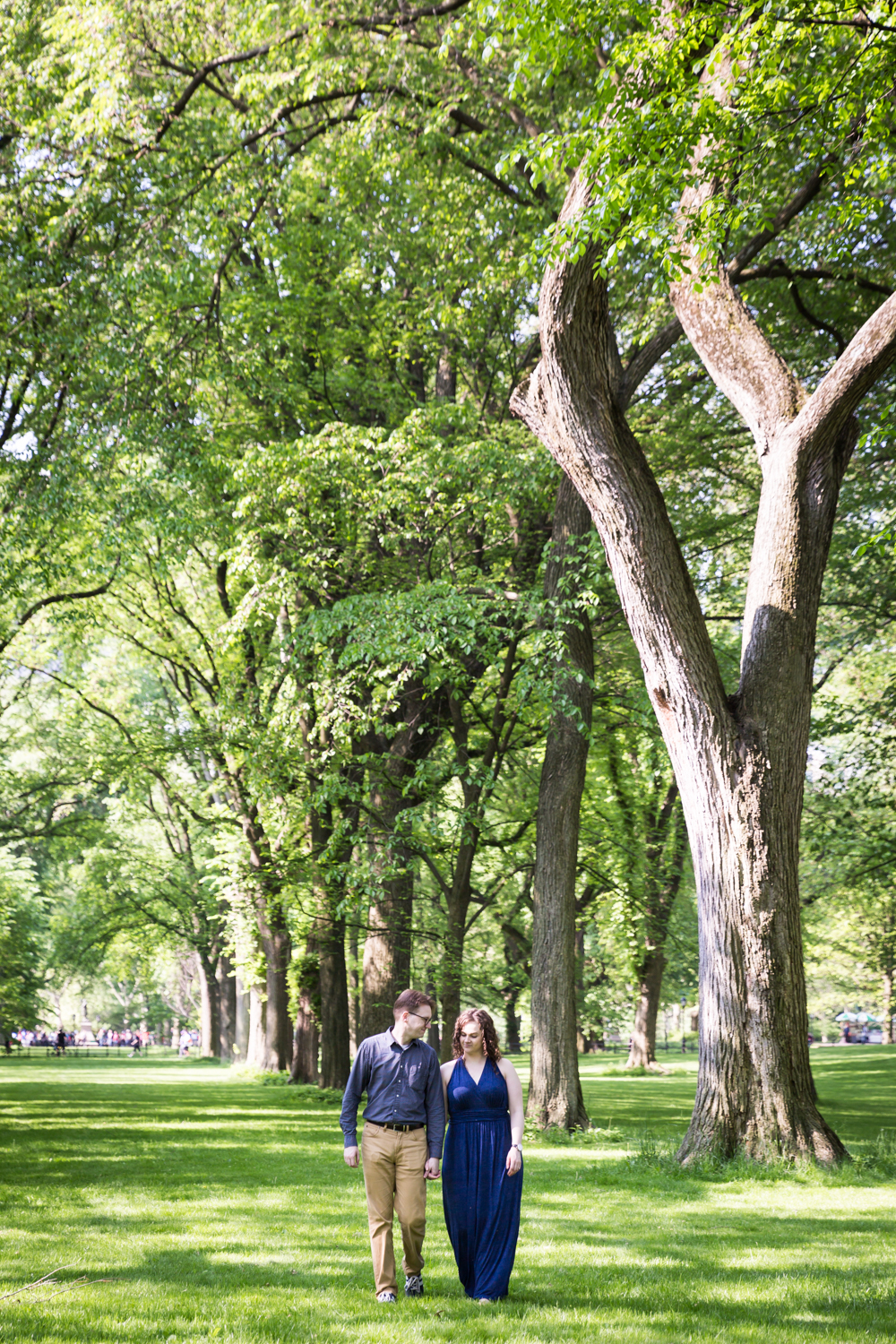 Couple walking underneath trees at the Central Park Mall in Shakespeare Garden engagement photos