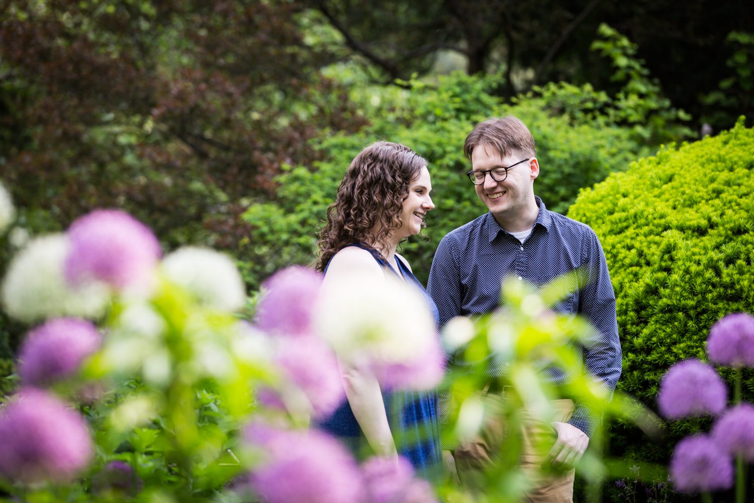Couple walking past colorful flowers in Shakespeare Garden engagement photos