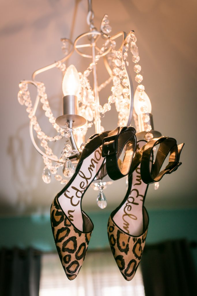 Pair of leopard print Sam Edelman heels hanging in a chandelier