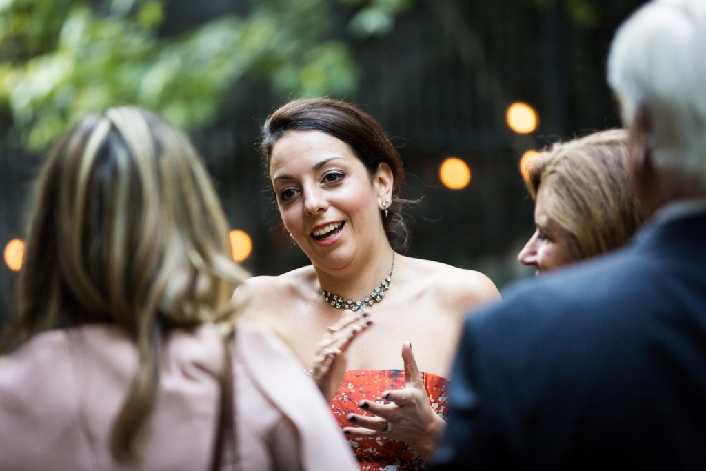 Guest talking to other guest at Central Park wedding cocktail party