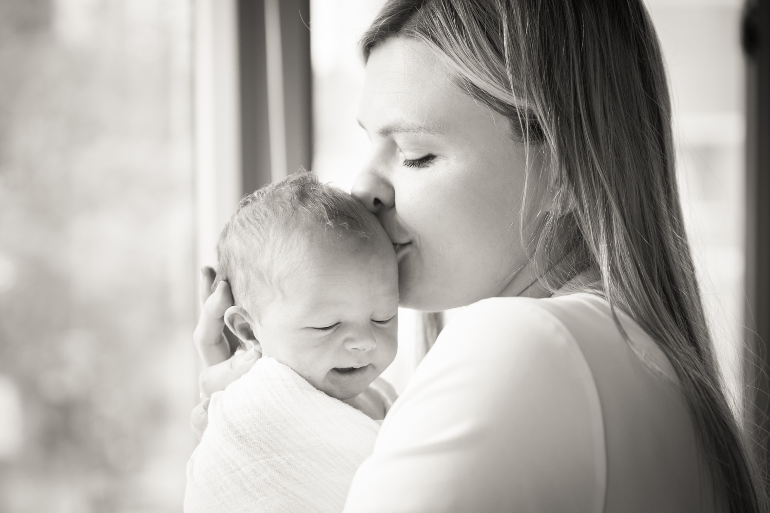 Black and white photo of mother kissing baby on side of head