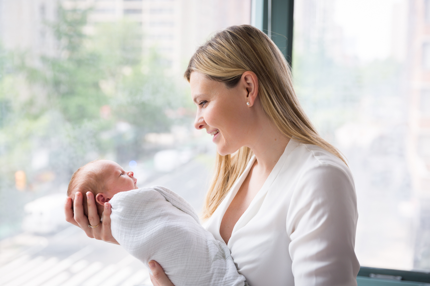 Mother holding newborn baby in front of window for an article on newborn portrait tips