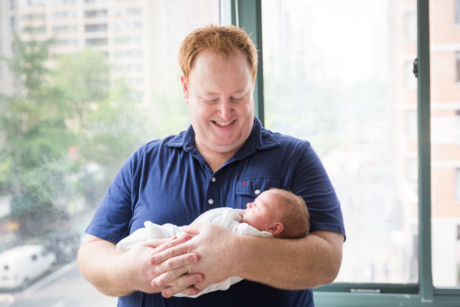 Father holding newborn baby in front of window for an article on newborn portrait tips