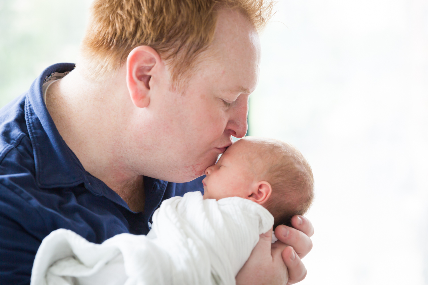 Close up of father kissing newborn baby on the forehead