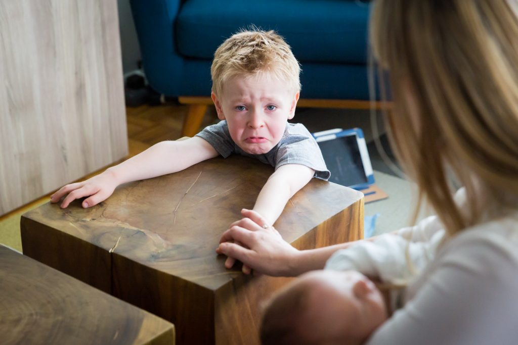 Little boy about to cry and sitting at table
