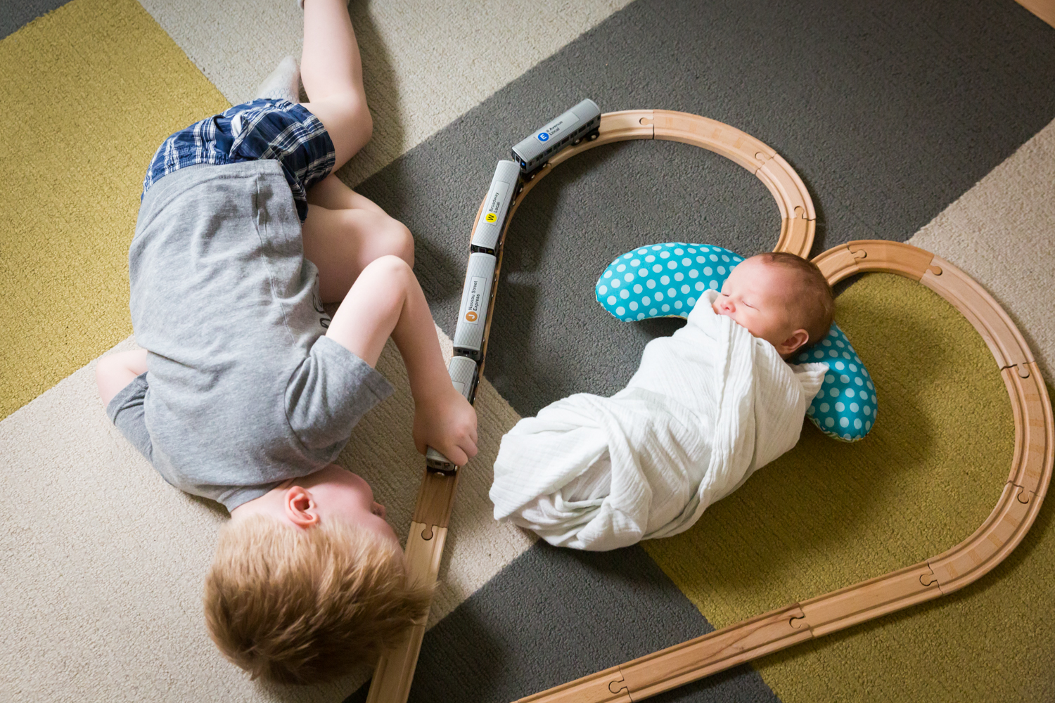 Little boy looking at newborn baby in middle of railroad toy set
