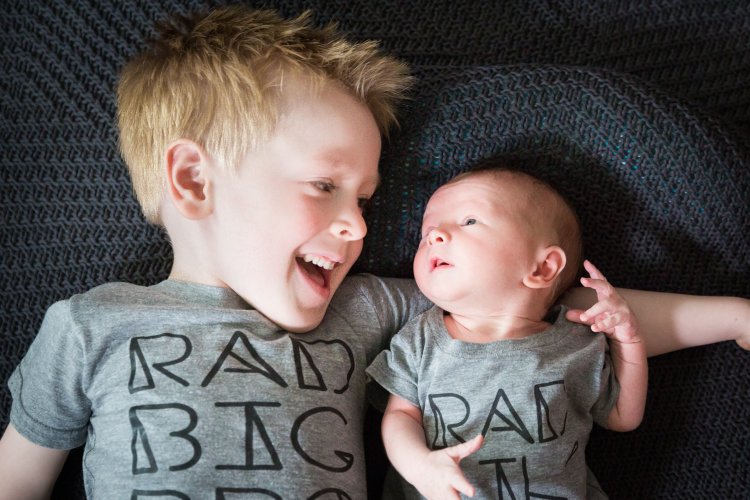 Little boy looking at newborn baby and wearing similar t-shirts