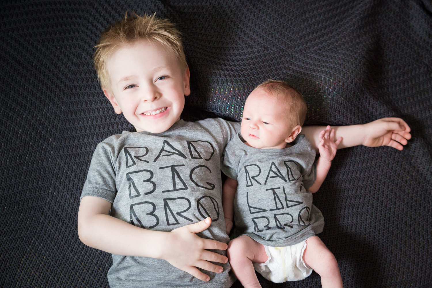 Little boy and newborn baby wearing matching grey t-shirts
