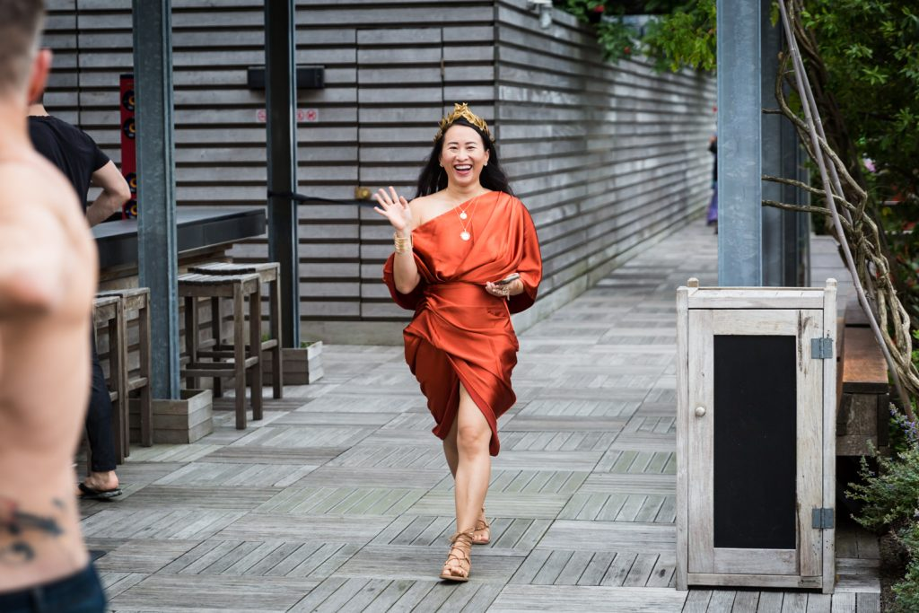 Birthday party photography of woman in orange wrap dress walking