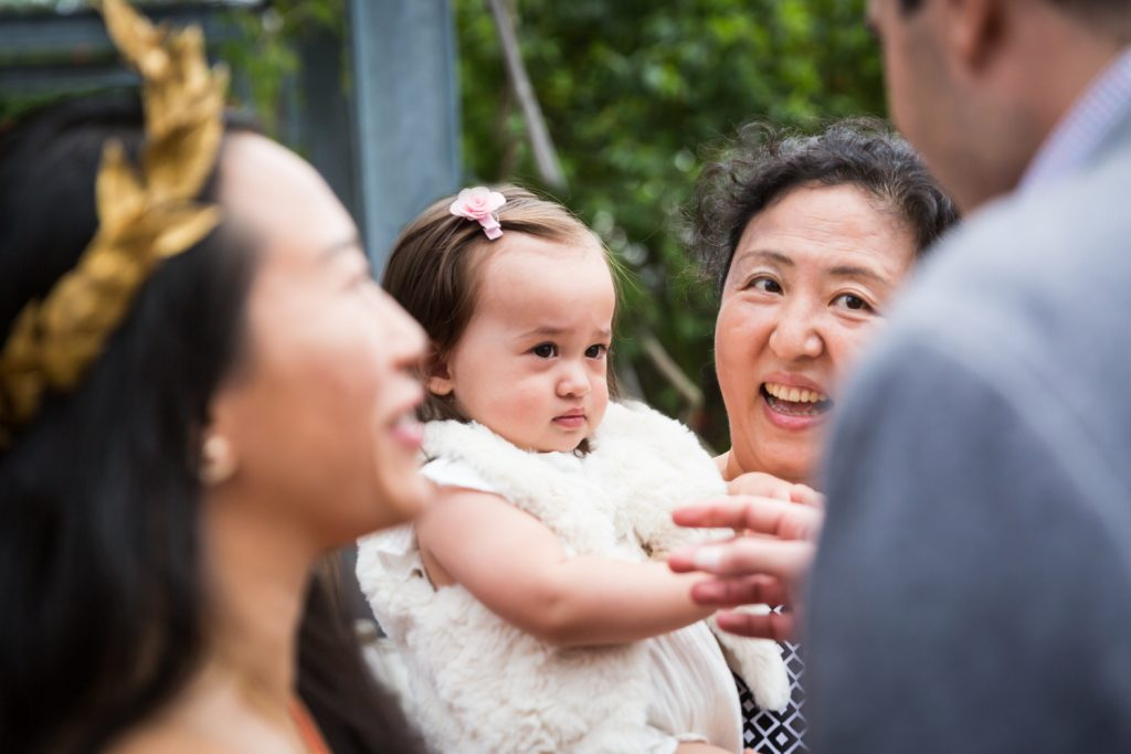 Birthday party photography of woman holding unhappy baby
