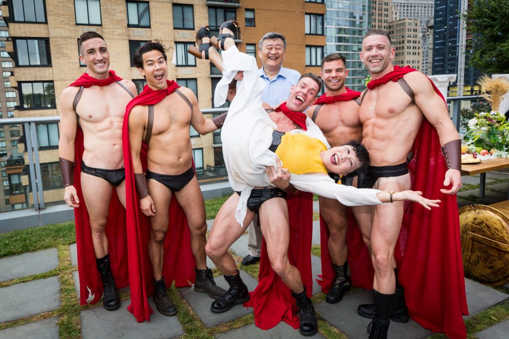 Birthday party photography of men dressed as gladiators holding older woman upside down