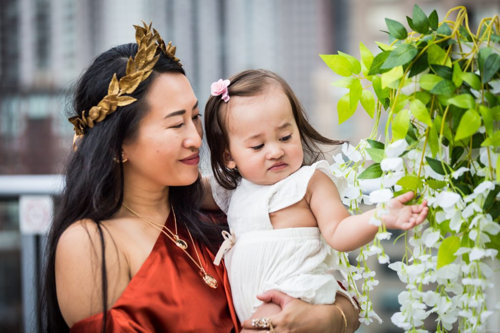 Birthday party photography of woman wearing gold laurel crown holding baby