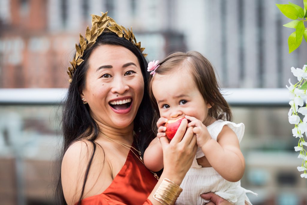 Birthday party photography of woman wearing gold laurel crown holding baby eating apple