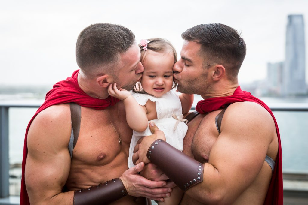 Birthday party photography of two men dressed as gladiators kissing little girl on both cheeks