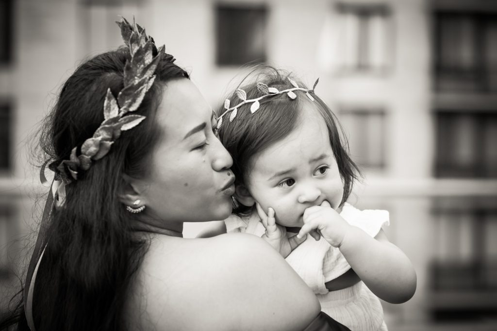 Black and white photo of mother holding little girl with both wearing laurel crowns
