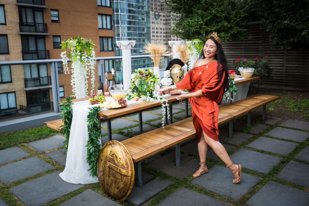 Birthday party photography of woman in orange dress posed by food buffet