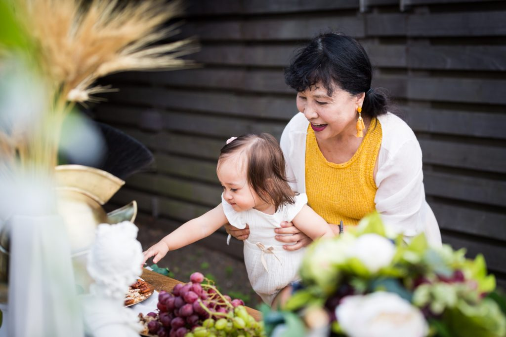 Birthday party photography of grandmother holding baby in front of food buffet