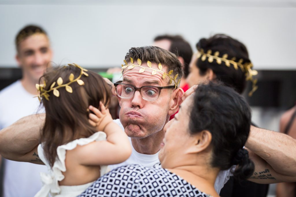 Man wearing laurel crown making funny faces in front of baby