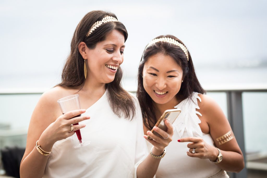 Two women dressed in toga outfits looking at cell phone
