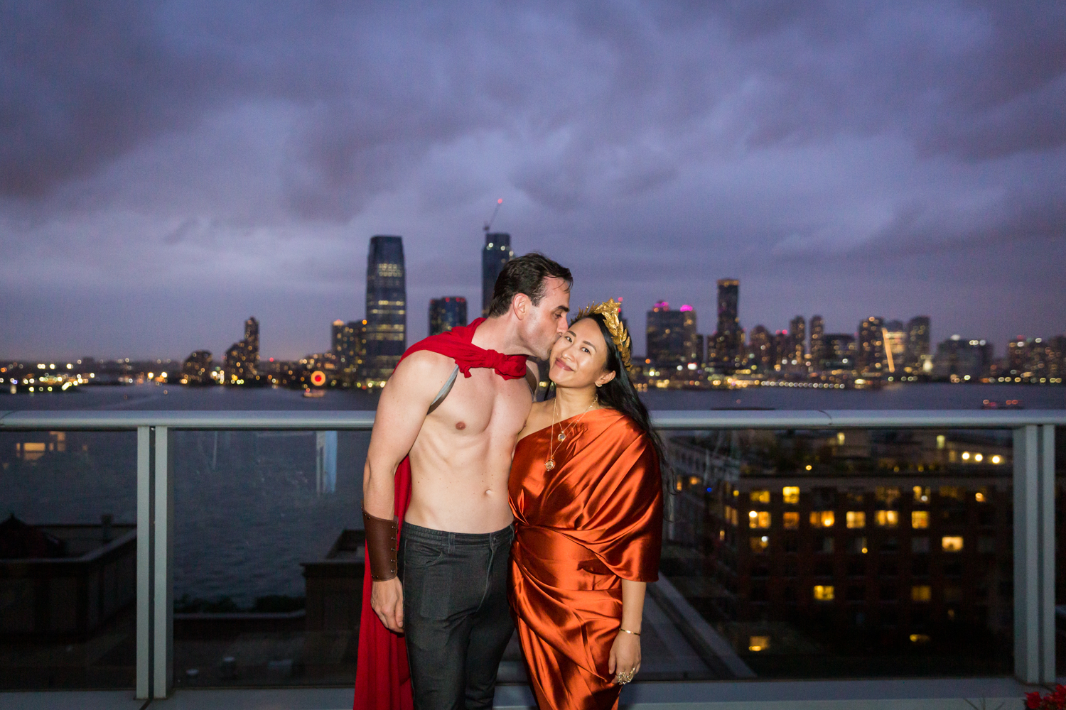 Man kissing woman at night wearing Roman outfit with NYC skyline in background