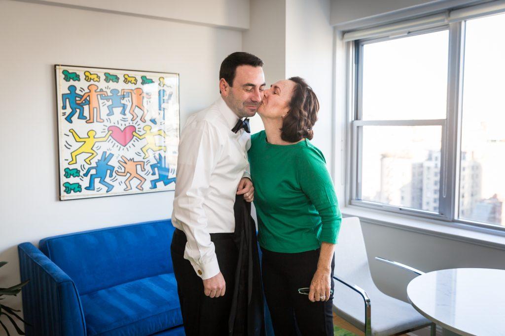 Mother kissing man in tuxedo by window