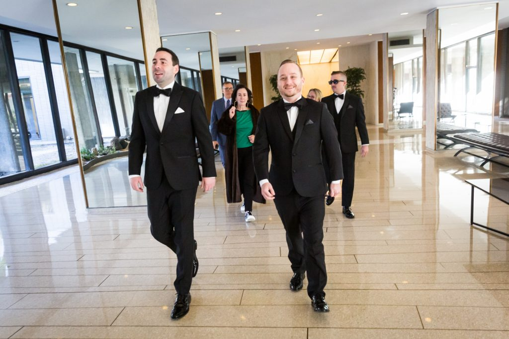 Groom and bridal party walking in apartment lobby at a Water Club wedding