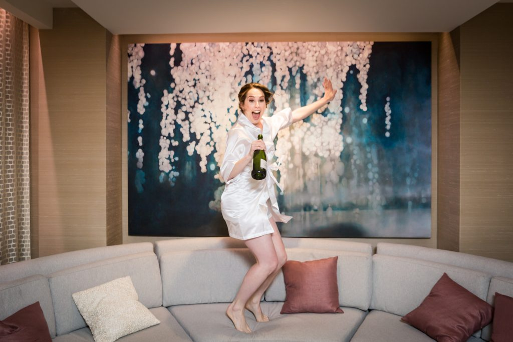 Bride jumping on couch with champagne bottle in hand at a Water Club wedding