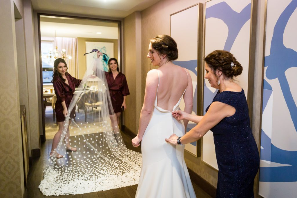 Mother zipping bride into her dress and sisters holding veil