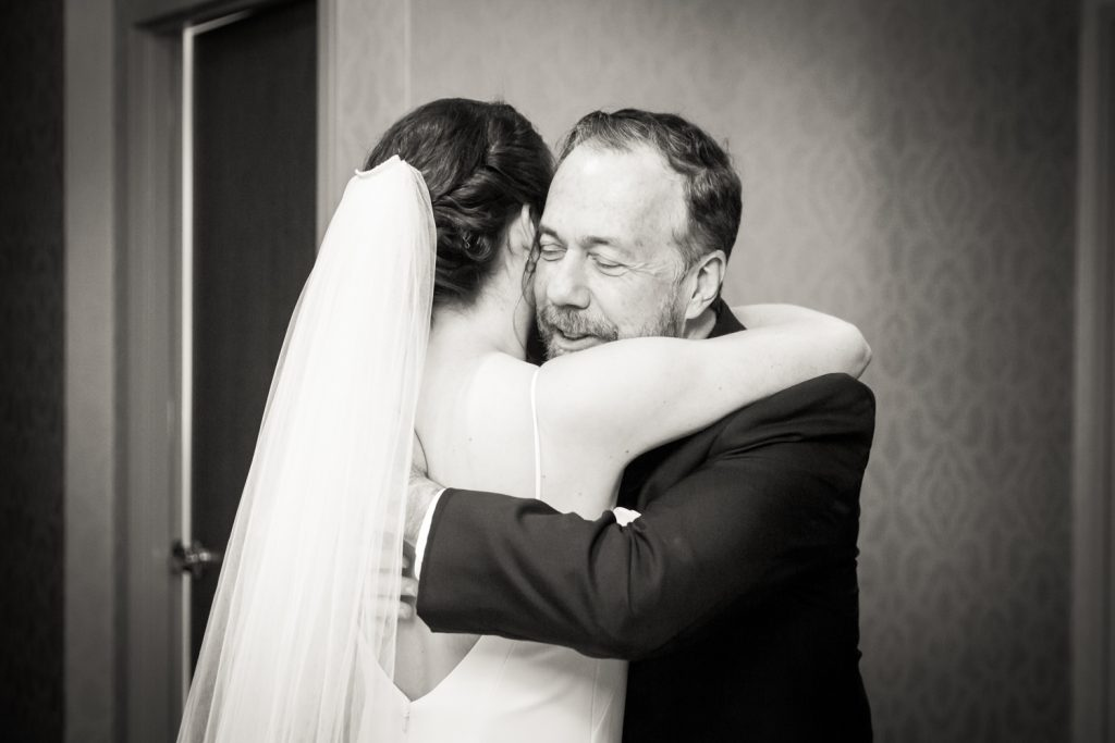 Black and white photo of father hugging bride