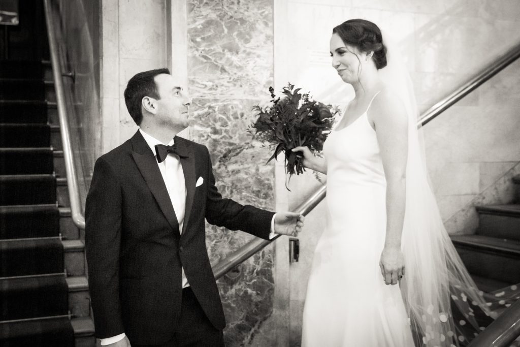 Black and white photo of groom seeing bride for first time at first look