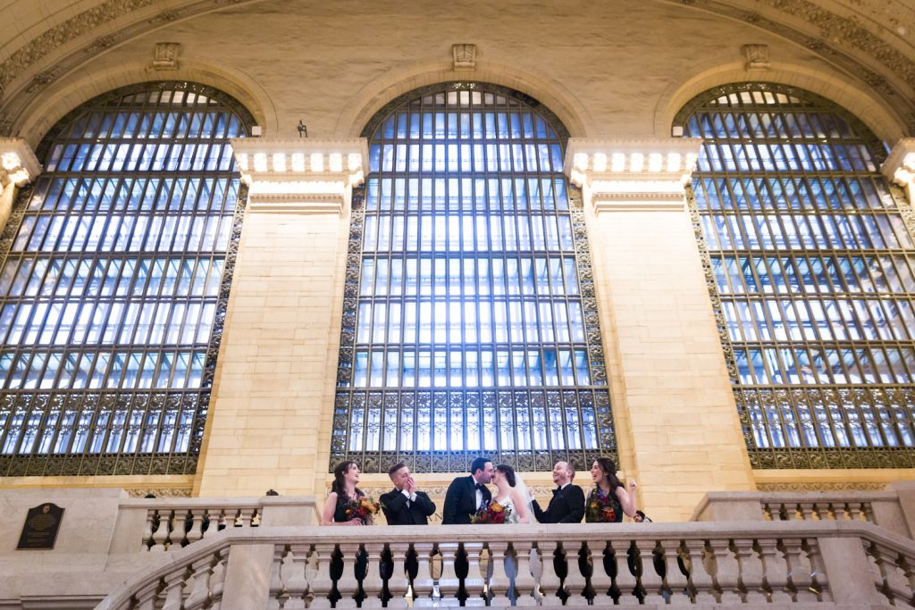 Bride and groom kissing with bridal party around on staircase at Grand Central Terminal