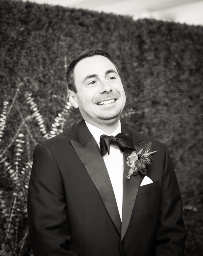 Black and white photo of groom waiting for bride at a Water Club wedding