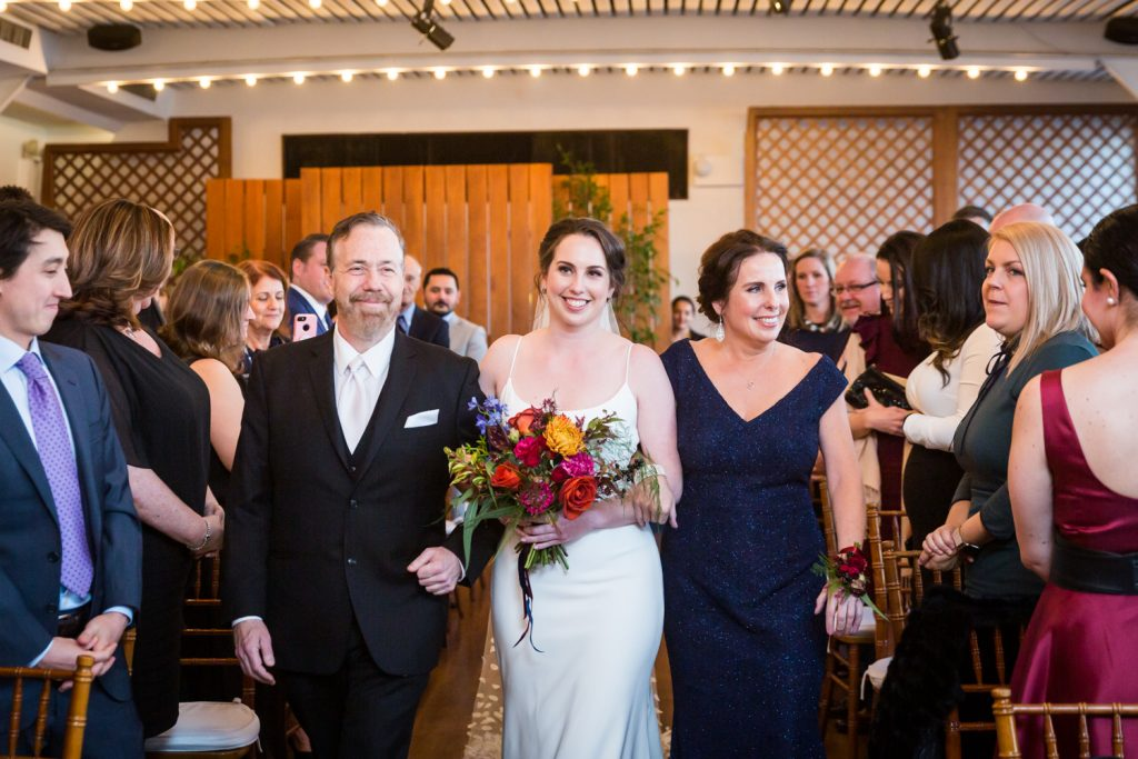 Bride escorted by both parents coming down aisle at a Water Club wedding