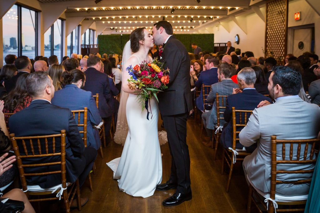 Bride and groom kissing at end of aisle at a Water Club wedding