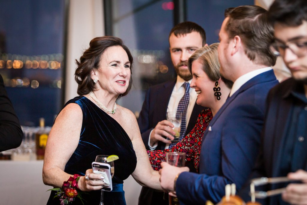 Woman wearing one-shouldered dress talking to guests at cocktail hour