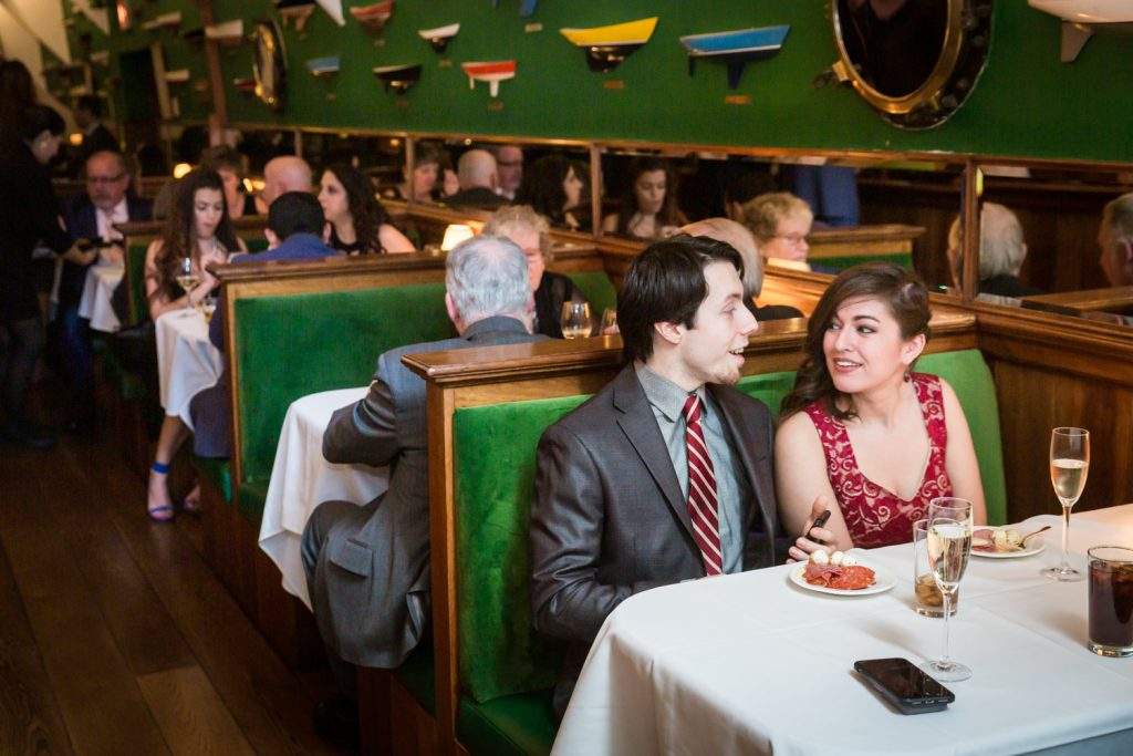 Guests sitting in booth during cocktail hour at a Water Club wedding