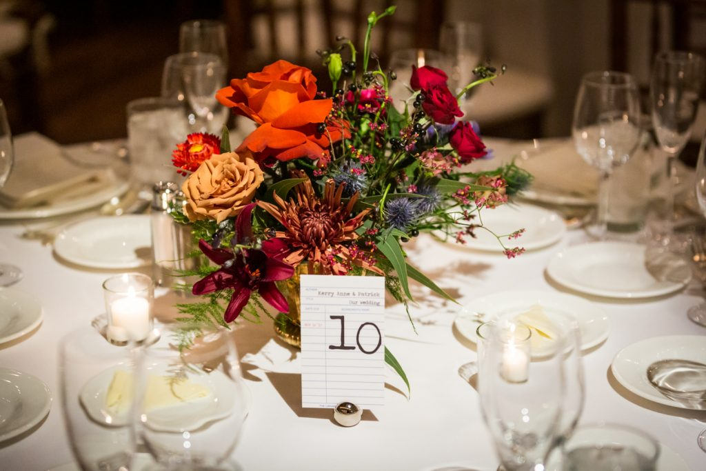 Floral centerpiece and card catalog table number at a Water Club wedding