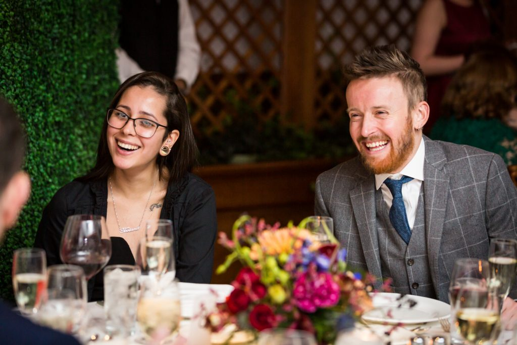 Two guests at a table laughing at a Water Club wedding